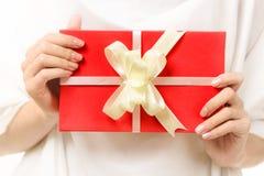 与一把弓的红色礼物在女性手上 库存照片