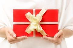 与一把弓的红色礼物在女性手上 免版税库存照片