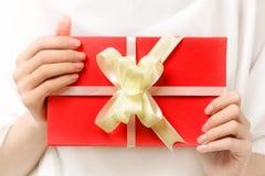 与一把弓的红色礼物在女性手上 免版税图库摄影