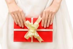 与一把弓的红色礼物在女性手上 免版税库存图片