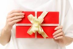 与一把弓的红色礼物在女性手上 库存图片