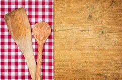 与一把方格的桌布和木匙子的土气木背景 免版税库存图片