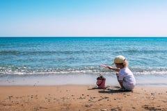 与一把桃红色塑料桶和铁锹的儿童游戏在海滩 图库摄影