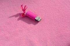 与一把桃红色弓的精采桃红色usb闪存卡片在软和毛茸的浅粉红色的羊毛织品毯子说谎  经典女性 免版税库存照片