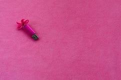 与一把桃红色弓的精采桃红色usb闪存卡片在软和毛茸的浅粉红色的羊毛织品毯子说谎  经典女性 库存图片