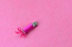 与一把桃红色弓的精采桃红色usb闪存卡片在软和毛茸的浅粉红色的羊毛织品毯子说谎  经典女性 免版税图库摄影