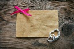 与一把桃红色弓的纸标记,两银色心脏 图库摄影