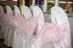 与一把桃红色弓的装饰的白色缎椅子 免版税库存照片