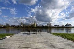 与一把沙滩伞的表在河岸的一个木码头 库存图片