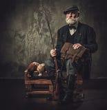 与一把猎枪和野鸡的资深猎人在传统射击衣物,在黑暗的背景的开会 库存照片
