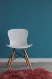 与一把现代白色椅子的室内设计场面在蓝色墙壁上 免版税库存照片