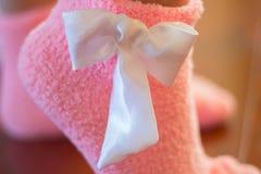 与一把白色弓的柔和的桃红色袜子 库存图片