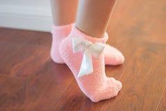 与一把白色弓的柔和的桃红色袜子 图库摄影
