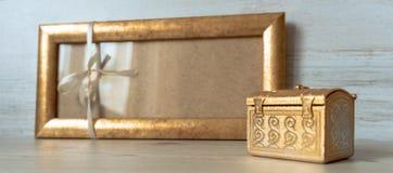 与一把白色弓的金黄框架和在灰色木背景的金黄胸口 免版税库存图片