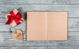 与一把红色弓、心脏和一本开放日志的礼物 浪漫概念 模板和背景 库存图片
