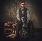 与一把英国塞特种猎狗和猎枪在传统射击衣物,在黑暗的背景的开会的英俊的猎人 免版税图库摄影