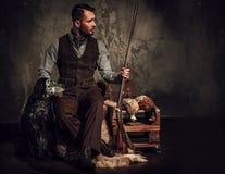 与一把英国塞特种猎狗和猎枪在传统射击衣物,在黑暗的背景的开会的英俊的猎人 图库摄影