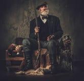 与一把英国塞特种猎狗和猎枪在传统射击衣物,在黑暗的背景的开会的资深猎人 免版税库存照片