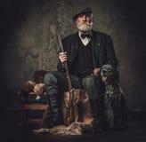 与一把英国塞特种猎狗和猎枪在传统射击衣物,在黑暗的背景的开会的资深猎人 库存图片