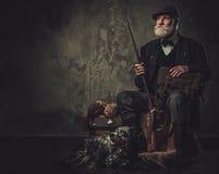 与一把英国塞特种猎狗和猎枪在传统射击衣物,在黑暗的背景的开会的资深猎人 库存照片