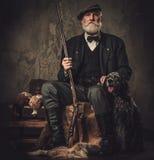 与一把英国塞特种猎狗和猎枪在传统射击衣物,在黑暗的背景的开会的资深猎人 免版税库存图片