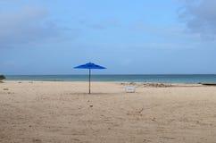 与一把蓝色伞的离开的海滩在一个白色沙子海滩 免版税图库摄影