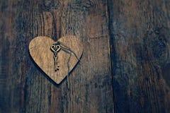 与一把钥匙的木心脏在木头构造了背景 免版税库存照片