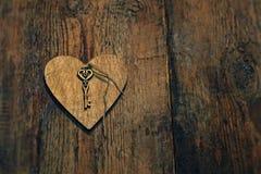 与一把钥匙的木心脏在木头构造了背景 免版税图库摄影