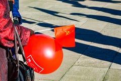 与一把镰刀和锤子的红色共产主义旗子在一个人的手上 库存图片