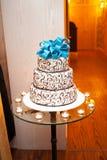 与一把绿松石弓的美丽的白色三层的蛋糕在上面在桌上 免版税库存照片