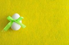 与一把绿色弓的一个白色复活节彩蛋 图库摄影