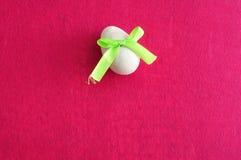 与一把绿色弓的一个白色复活节彩蛋 免版税图库摄影