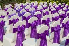 与一把紫色弓的椅子在一个美好的婚礼 免版税库存照片