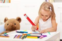 与一支大铅笔的小女孩图画-坐在桌上 免版税库存照片