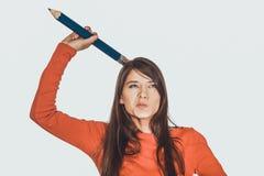 与一支大铅笔的美丽的年轻人在头 库存照片