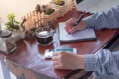 与一支笔的商人文字在笔记本 库存照片