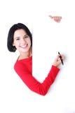 与一支笔的愉快的妇女文字在空白董事会。 免版税库存照片