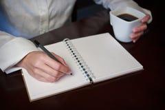 与一支笔的手文字在一个笔记本用附近的咖啡 免版税图库摄影