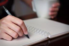 与一支笔的手文字在有被弄脏的附近咖啡杯的一个笔记本  免版税库存照片
