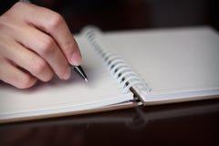与一支笔的手文字在笔记本 免版税库存照片