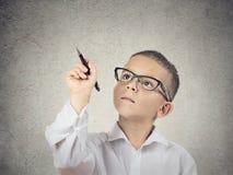 与一支笔的男孩文字在黑板 库存照片