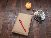 与一支笔的笔记薄在一张木桌上 免版税图库摄影