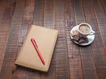 与一支笔的笔记薄在一张木桌上 库存图片