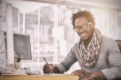 与一支红色铅笔的微笑的设计师图画在书桌上 免版税库存照片