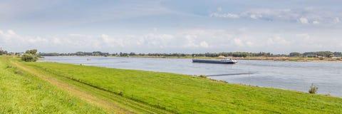 与一支运输船的被覆盖的河风景在的一条河 库存照片