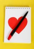 与一支黑笔的红色心脏在白色笔记本 免版税库存图片