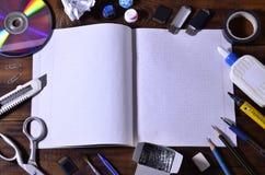 与一本开放学校笔记本的一幅学校或办公室静物画或支票簿和许多办公用品 在增殖比的学校用品谎言 免版税库存照片
