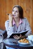 与一本日志的女孩尖酸的笔在咖啡馆 库存图片