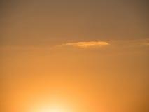 与一朵偏僻的云彩的金黄天空 免版税图库摄影