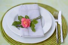 与一朵唯一桃红色玫瑰的浪漫餐位餐具 库存照片